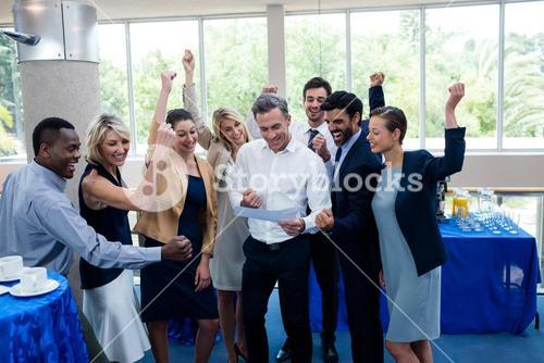 Happy business executives looking at report
