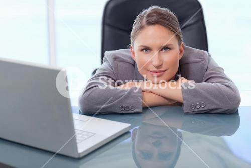 Businesswoman leaning on her desk