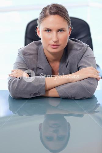 Portrait of a serious businesswoman leaning on her desk