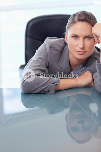 Portrait of a bored businesswoman leaning on her desk
