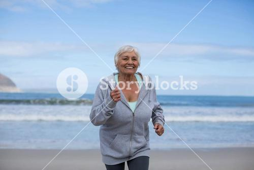 Senior woman jogging on the beach