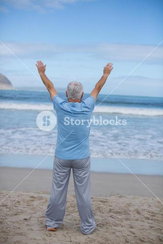 Senior man doing stretching exercise on the beach