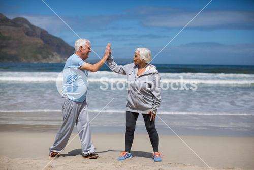 Senior couple giving high five after exercise on the beach