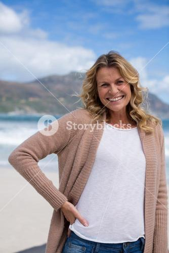 Mature woman with hands behind head standing on the beach