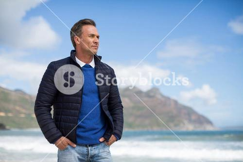 Man standing on the beach looking at ocean