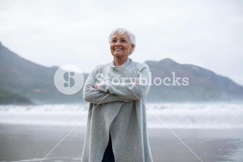 Senior woman standing with arms crossed on the beach