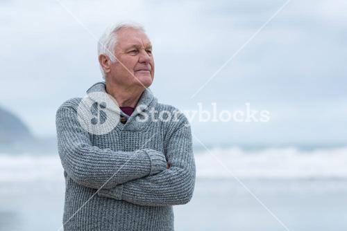Senior man standing with arms crossed on the beach