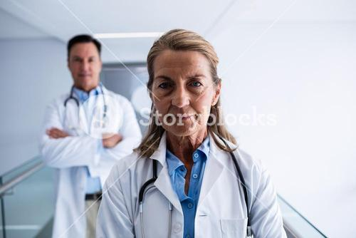 Portrait of female and male doctor standing in the passageway