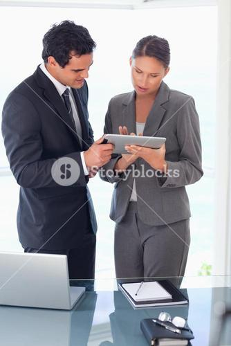 Tradesman explaining functionality of tablet to his colleague