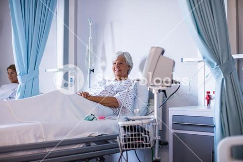 Female senior patient smiling and relaxing on a bed in the ward