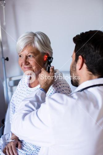 Doctor examining patients ear with otoscope