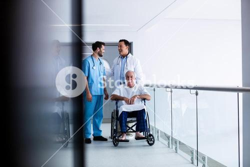 Doctors interacting each other with patient on wheelchair in passageway