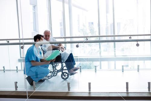 Doctor interacting with male senior patient in passageway