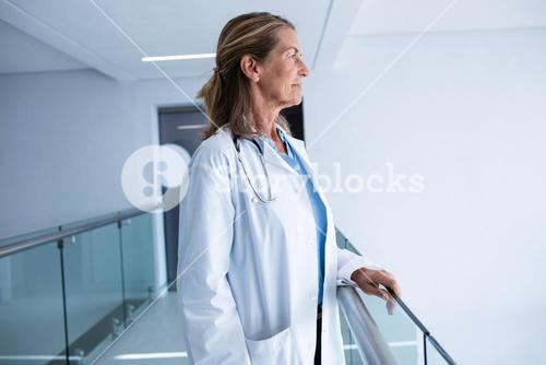 Thoughtful female doctor standing in passageway