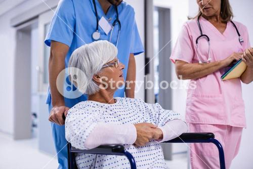Male and female doctor interacting with female senior patient on wheelchair in corridor