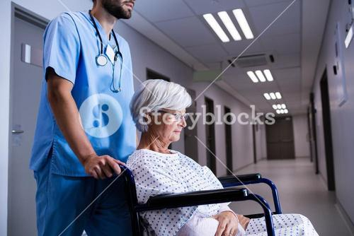 Male doctor pushing senior patient on wheelchair to the ward