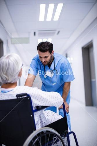 Male doctor interacting with senior patient on wheelchair
