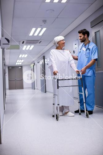 Male doctor assisting senior patient to walk with her walker