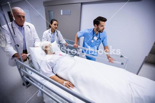 Doctor and nurse pushing emergency stretcher bed in corridor