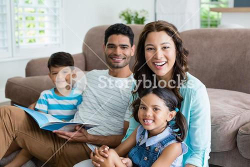 Portrait of parents and children sitting on sofa and reading book