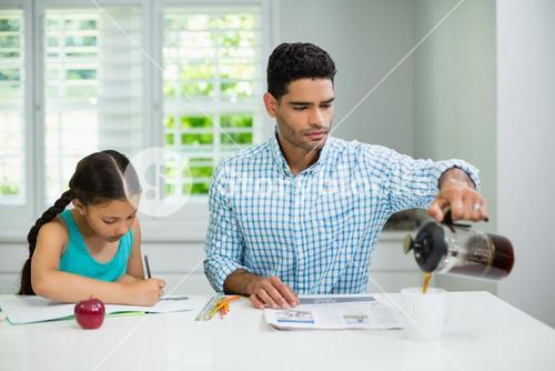 Daughter doing her homework and father pouring black tea in cup while reading newspaper