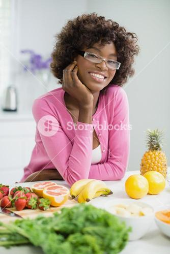 Beautiful woman leaning with hand on face in kitchen