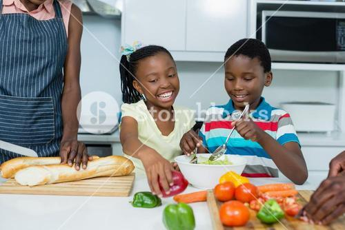 Kids preparing salad while mother cutting bread loaf in kitchen