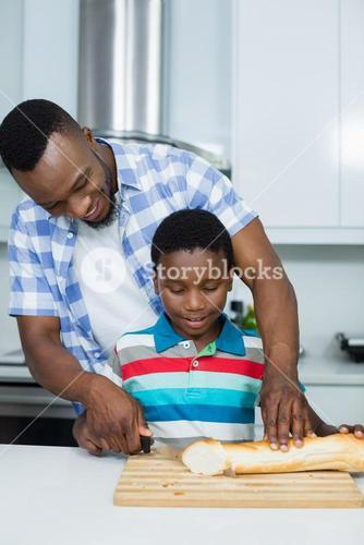 Father assisting his son in cutting loaf bread in kitchen