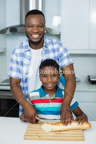 Father assisting his son in cutting loaf bread in kitchen at home