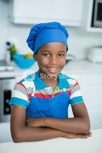 Smiling boy in chefs hat at home