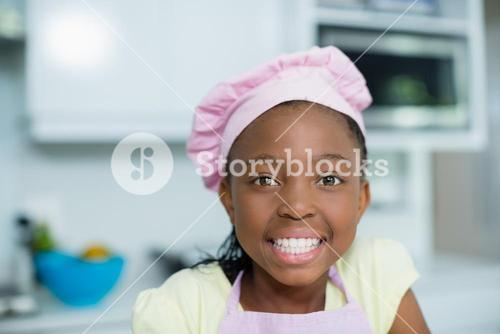 Smiling girl in chefs hat at home