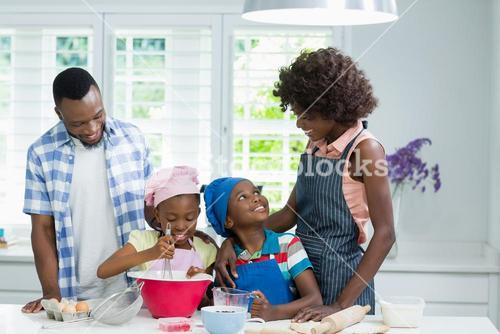 Parents and kids preparing food in kitchen