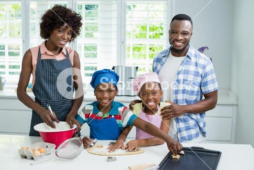 Parents and kids preparing food in kitchen at home