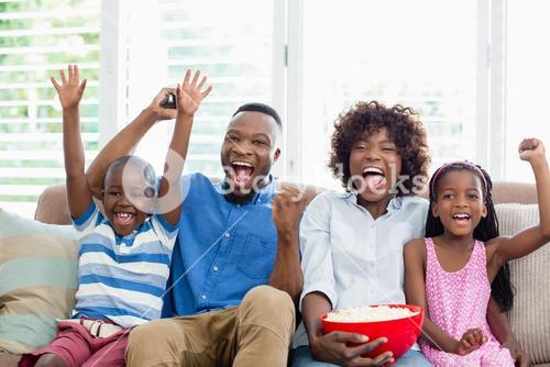 Excited family and kids watching television while having popcorn in living room