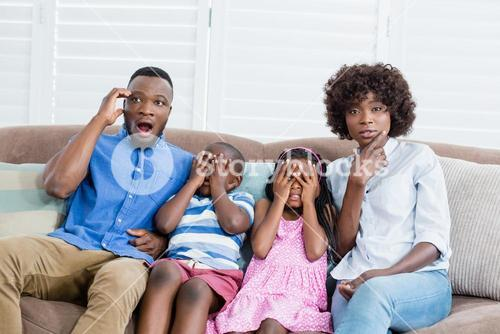 Family and kids watching television while having popcorn in living room at home