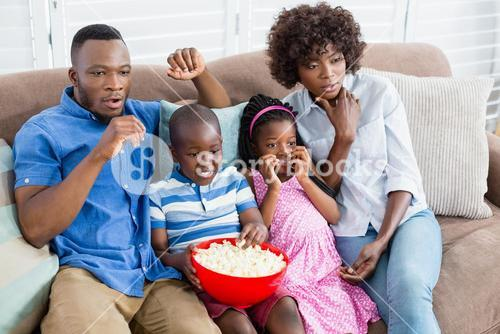 Family and kids watching television while having popcorn in living room