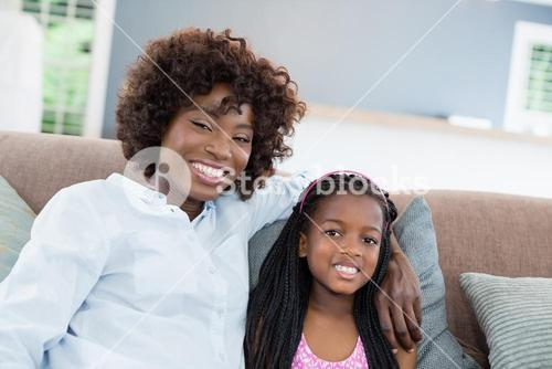 Portrait of mother and daughter sitting on sofa in living room