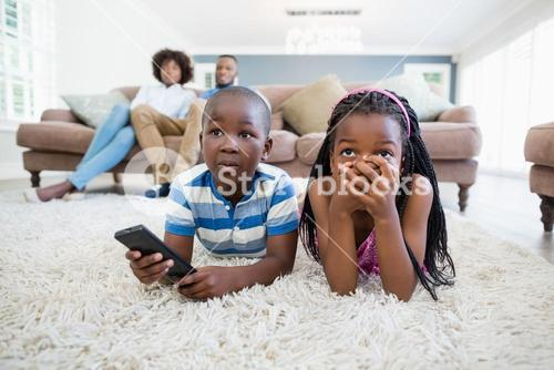 Siblings lying on rug and watching television in living room