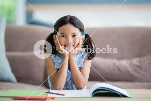 Portrait of girl sitting with hand on face in living room