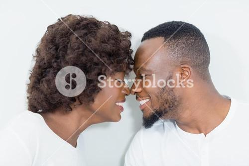 Couple romancing face to face in bedroom