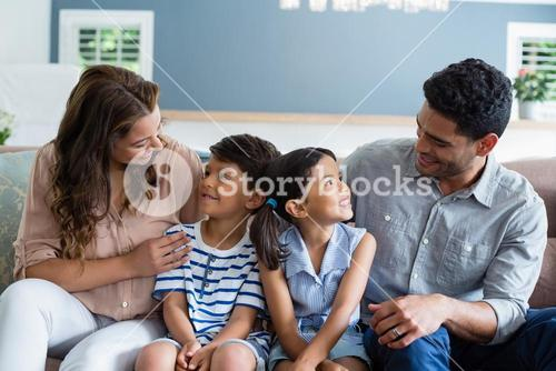 Parents and kids interacting on sofa in living room