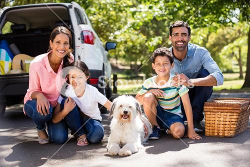 Happy family on a picnic sitting next to their car