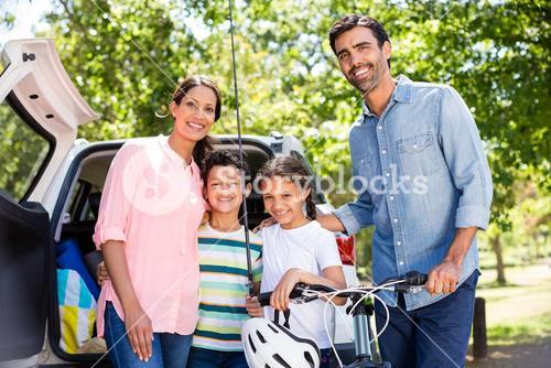 Happy family on a picnic standing next to their car