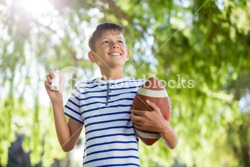 Smiling boy holding asthma inhaler and a rugby ball