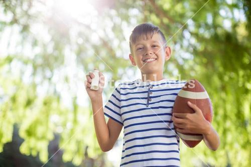 Boy holding asthma inhaler and a rugby ball