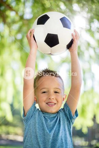 Portrait of boy holding a football in park