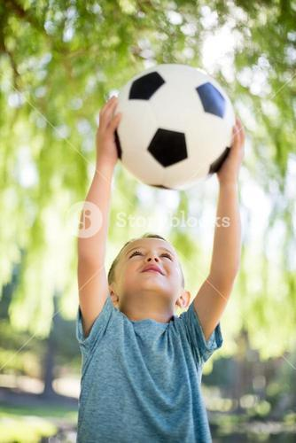 Boy playing with a football in park