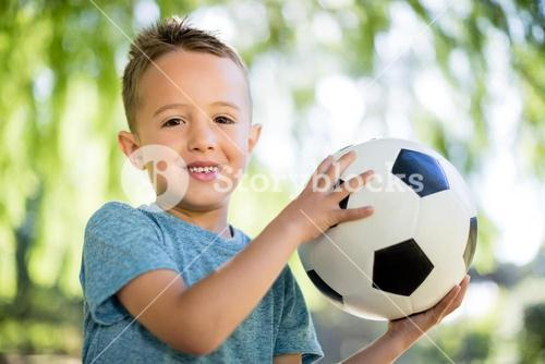Portrait of boy playing with a football in park