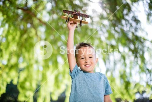 Portrait of boy playing with a toy aeroplane in park