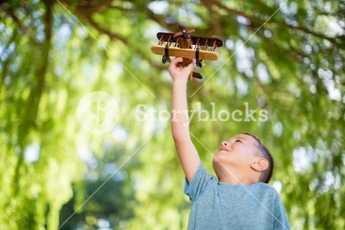 Boy playing with a wooden toy aeroplane in park